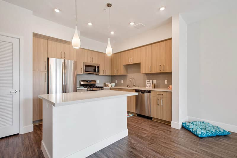 The Crossings of Chino Hills kitchen area showing counter table, cabinets, wood style flooring