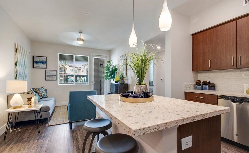 kitchen with hanging lights and living room in distance