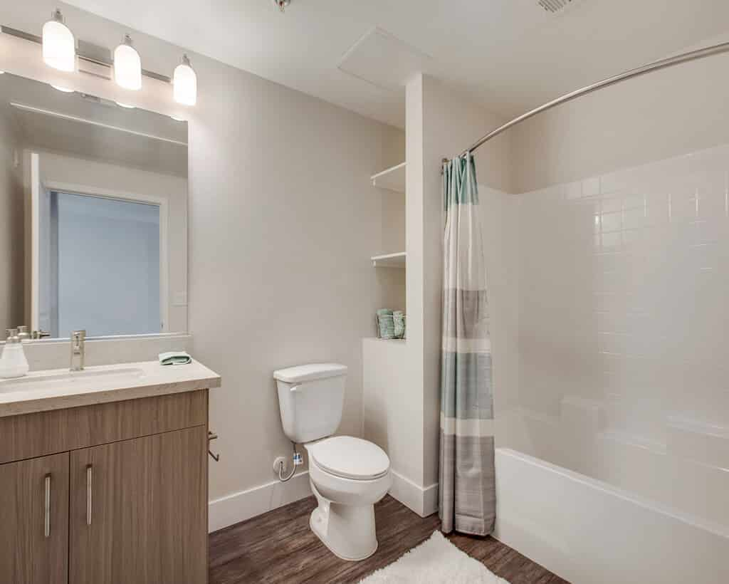 The Crossings of Chino Hills bathroom with curtain, toilet, mirror, bathtub and cabinet